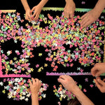 1000 Changing Colors Puzzle pieces dumped on black tabletop with hands from four people building border of puzzle.