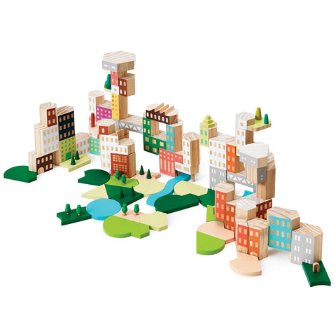 Against a white background is a photograph showing a side view of the building set. It is assembled to form a cityscape including buildings of varying shapes and sizes stacked together with some connected by bridges. In front of the buildings are several green spaces featuring grassy areas, trees and water.