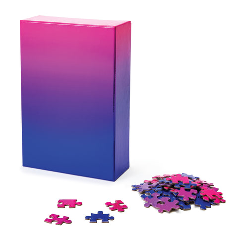 Gradient Puzzle box standing on an angle showing pink to blue gradation on box with a few sample puzzle pieces in a pile.