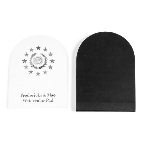 Above view of a water color pad shaped as an archway or composite shape of a semi circle and rectangle. The pad has a white front cover with the company name and logo and a solid black back cover
