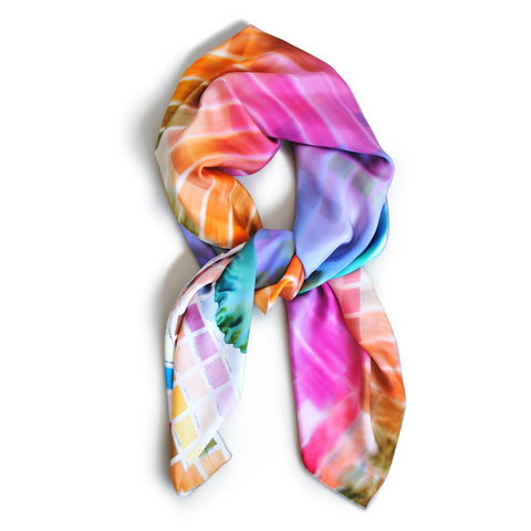 On Color Scarf; a knotted Rainbow silk scarf with the appearance of spilling colors on a white background.