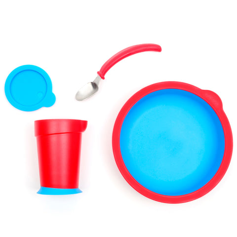 4-Piece assisted tableware set including a cup with lid, a spoon, and plate. The cup features a silicon base that helps with stability. The spoon handle is curved for easy grip and the plate features a slanted bottom. The set is blue and red.