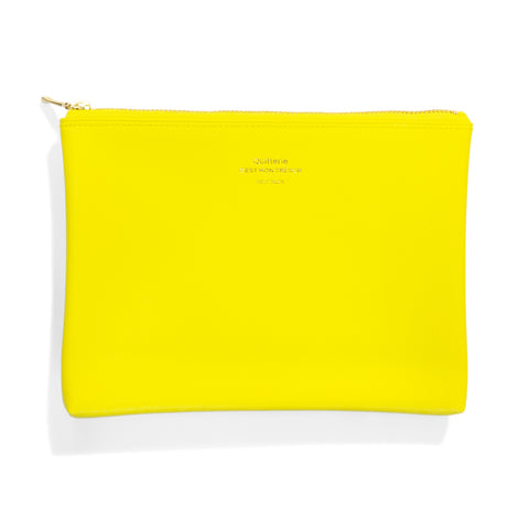 A flat, bright yellow rectangular pouch has a gold zipper across the top edge. The logo is embossed in gold onto the front of pouch.