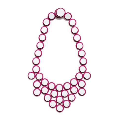 Necklace assembled from hexagons made from white acrylic and placed on top of bright pink suede underneath.