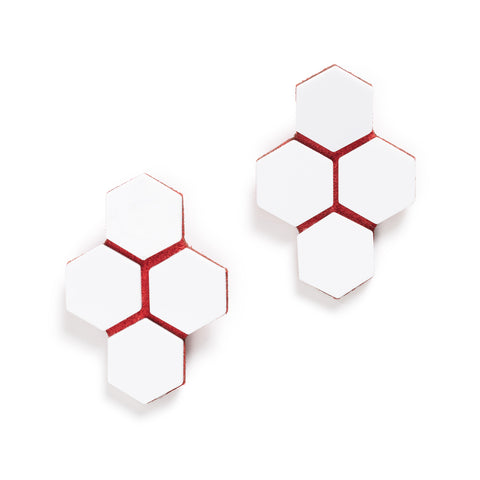 A pair of earrings with four hexagons made from white acrylic and placed on top of orange leather underneath .