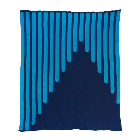 Throw blanket in two shades of blue. A vertical graphic design has been knitted into the fabric and resembles thick striped lines drawn at an angle. The stripes are a medium blue against a dark blue backdrop.