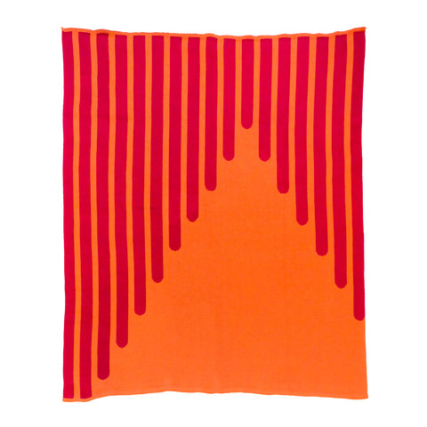 Throw blanket in orange with red stripes. A vertical graphic design has been knitted into the fabric and resembles thick striped lines drawn at an angle. The stripes are red against an orange backdrop.