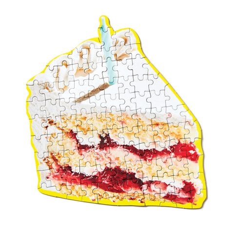 An assembled  puzzle in the shape of a slice of birthday cake with a candle on top.