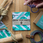 Know Your Knots Bandana placed on a wooden surface and surrounded by tools to make various knots. a light-skinned hand is featured at the top right of the image with a knot in-hand.