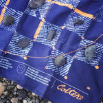 Cabin Fever Game Bandana with rocks used as playing pieces on its printed board game surface.