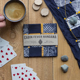 Cabin Fever Game Bandana placed on a wooden surface and surrounded by indoor activities including playing cards, and hot cocoa.