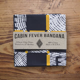 Cabin Fever Game Bandana wrapped in paper band packaging. The packaging includes black text that indicates the name of the item along with information about the product. The brand logo is diamond shaped, printed in black and centrally located on the packaging.