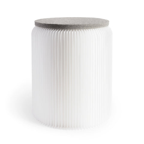 Softseat Stool Side view of a simple yet  elegant, white, cylinder-shaped stool made from a curved accordian of vertical paper pleats, topped by a gray felt disc seat.