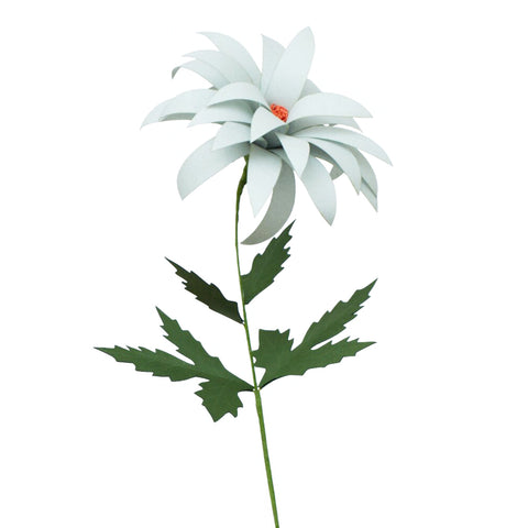 Against a white background, a photograph of a grey paper poppy with an orange center standing vertical with a green stem and green leaves.