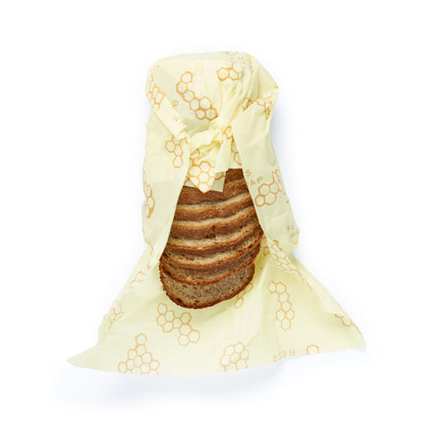 Slices of bread nestled inside a pale yellow cloth patterned with honeycomb shapes.