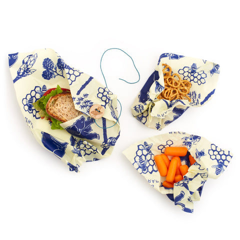 Ivory wraps with a repeating blue pattern of blue bees, berries, bears, and buds. A sandwich, a bunch of pretzels and a bunch of carrots are nestled in wrappers. The sandwich has a button and string closure.