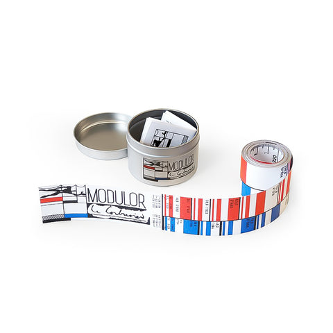 Coiled tape with black red and blue pattern with modulated measurements next to an opened cylindrical tin that houses the tape