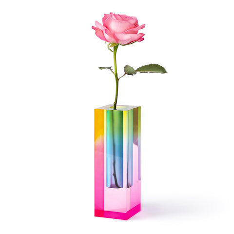 A translucent square block style bud vase emitting a prism of iridescent colors including shades of pink, blue, yellow and green. A single pink rose sits inside.