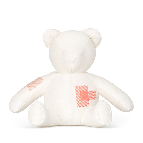 Front view of cream colored teddy bear with patchwork detail on right arm and stomach