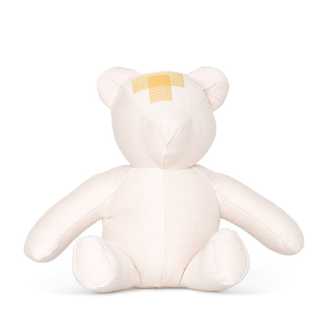 Front view of blush colored teddy bear with patchwork detail on forehead