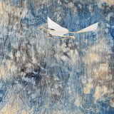 An ornithopter hangs by two strings like a mobile, in front blue white and grey abstract cloth.