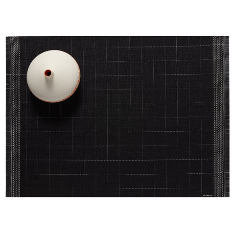 A woven rectangular mat, black with black fringe and a woven pattern of thin horizontal white lines with black & white striped borders. A round unfired ceramic vessel/pen holder is positioned in the upper left corner.