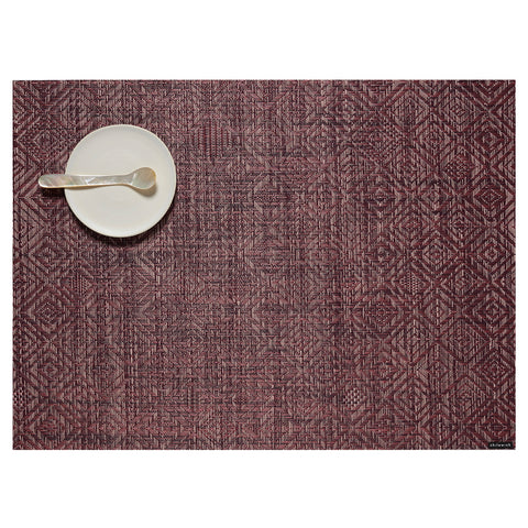 Overhead view of a plum, twill weave mat on a white background with a lattice pattern of unique, intersecting diamonds, with a small cream colored plate and mother of pearl spoon in the upper left corner.