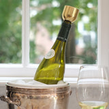 In front of a window, a wine bottle sits on an angle inside a silver ice bucket. It is capped with a Mass Wine Stopper. A glass of wine stands next to the bucket.