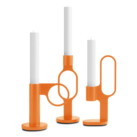 Set of three bright orange candlesticks each holding a white candle. The candlesticks are cylindrical, offering a different circle or oval shaped handle, with a sturdy disk base.