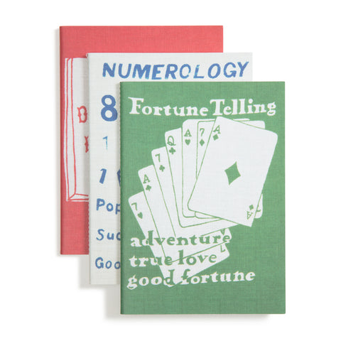 Marguerita Mergentime Notebooks, Set of 3 notebooks in red, white or green overlap one another and feature artwork form the Fortune Telling series. The partially visible middle notebook is white, and says Numerology in blue letters. The green notebook in front says Fortune Telling in white letters above an arrangement of six white playing cards with green suits, and the words adventure, true love and good fortune in white letters over green and green letters over white.
