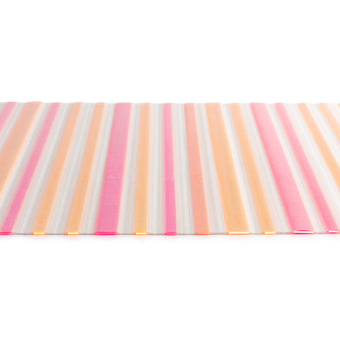 The Edges Placemat horizontal mat against a white background,  white woven mesh placemat with alternating insert strips of bright pink and melon  acrylic strips.