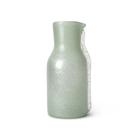 Light green glass bottle with a thick neck, the texture of small air bubbles is visible, decorated with a clear fin on one side.
