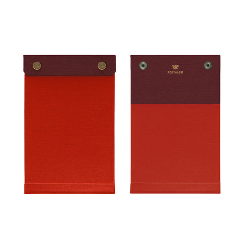 Front and back view of the palm-sized refillable notepad with snap closure in red with maroon border. The brand name and logo are embossed at center back in gold.