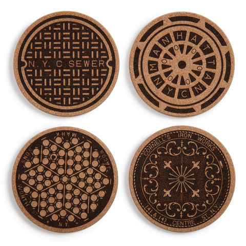 Set of four cork NYC Manhole Coasters on white background, each with a different historic manhole pattern in black.