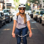 A women rides a bicycle down a city street wearing a white Fend helmet.