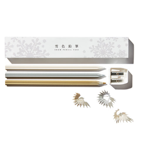 A Snow Pencil set with the box and its contents laid out on a white surface. The shot includes the white snowflake patterned box, three different color metallic pencils, and a white double sharpener. Pencil shavings are strewn about.