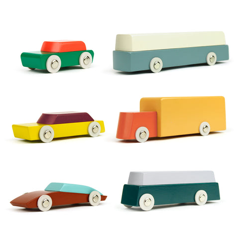 Profile view of 6 colorful two-tone wooden cars with white wheels and silver metal hub caps. Arranged in three rows with one car and one bus/truck/trailer per row. Orange and green car and white/light blue bus, brown and yellow sedan car and orange and mustard colored truck, brown and aqua sports car and grey and deep green trailer