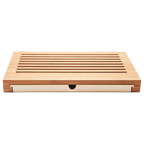 Rectangular shaped bread board in light colored wood with slits for crumbs to fall into a pull-out plastic drawer with finger-sized cut-out to pull out with ease.