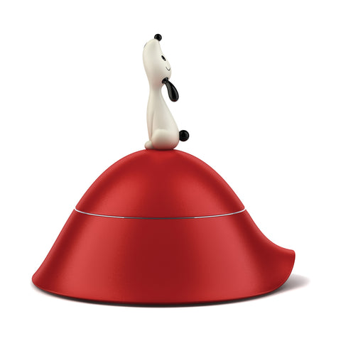 Red bowl shaped like a hill with small howling black and white dog