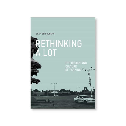 Book cover with photograph in tones of light blue and gray showing a large parking lot with a white cab and a partially obscured stack of cars as a statue to the left. Title in white near the top