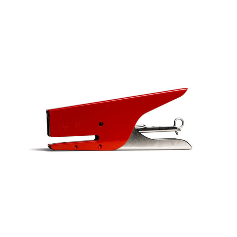 "An image of a red and silver metal stapler with a shape that is reminiscent of a whale. The left side has a mouth-like slot for papers. The handle spreads open to the right and resembles a tail. A black screw appears to be an ""eye""."