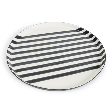 Handmade large porcelain plate, glazed with 9 black lines across the center of the plate covering a white backdrop.