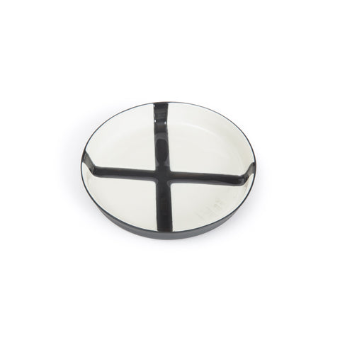 Glazed porcelain flat saucer with low rim. Black cross detail across a white base.