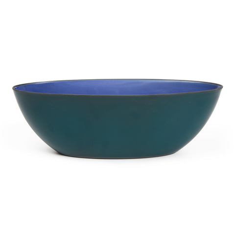 A medium sized boat shaped porcelain two tone bowl featuring a royal blue interior and a dark green exterior.