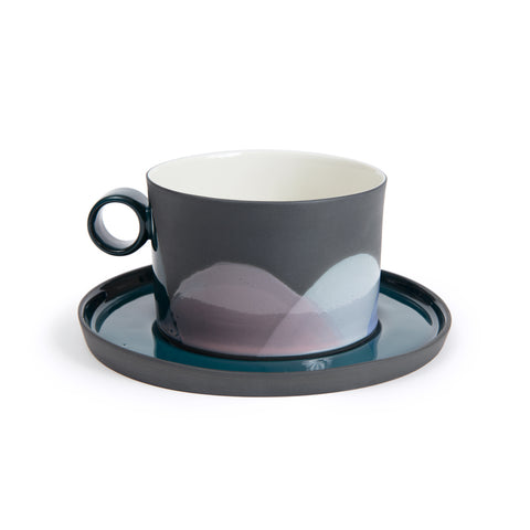 Wide rimmed handmade porcelain coffee cup with circular handle, resting atop a glazed porcelain saucer. The coffee cup has a circular dip detail at the base. The saucer features a dark teal interior and gray exterior.