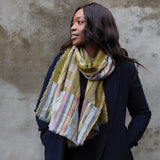3/4 view of a dark skinned female model in profile with shoulder length hair, posed against a mottled gray wall, wearing a long sleeved navy coat and a Penfold Wool Wrap draped around her neck with asymmetric double-cloth blocks of color and pattern.