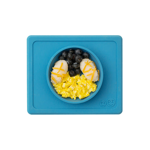An overhead view of all-in-one rectangular blue silicone bowl and placemat against a white background shown with a child's meal of egg salad, blueberries and potatoes with cheese shreds