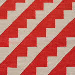 Detail of rug with diagonal saw tooth orange lines against beige background showing handwoven texture