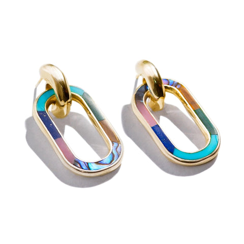 Quarter view of two gold colored, double-hoop earrings with iridescent, chromatic, multi-stone inlay on a white background