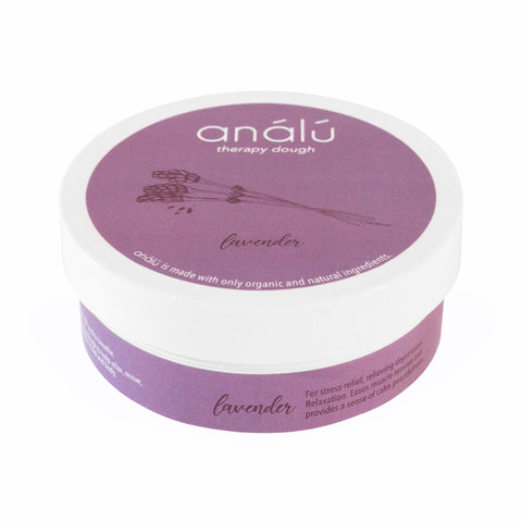 A small container with purple packaging. There is white text on the lid that reads 'análú therapy dough. A small drawing of dried lavender is displayed underneath the text, indicating the scent. There is also text around the body of the container indicating its use.
